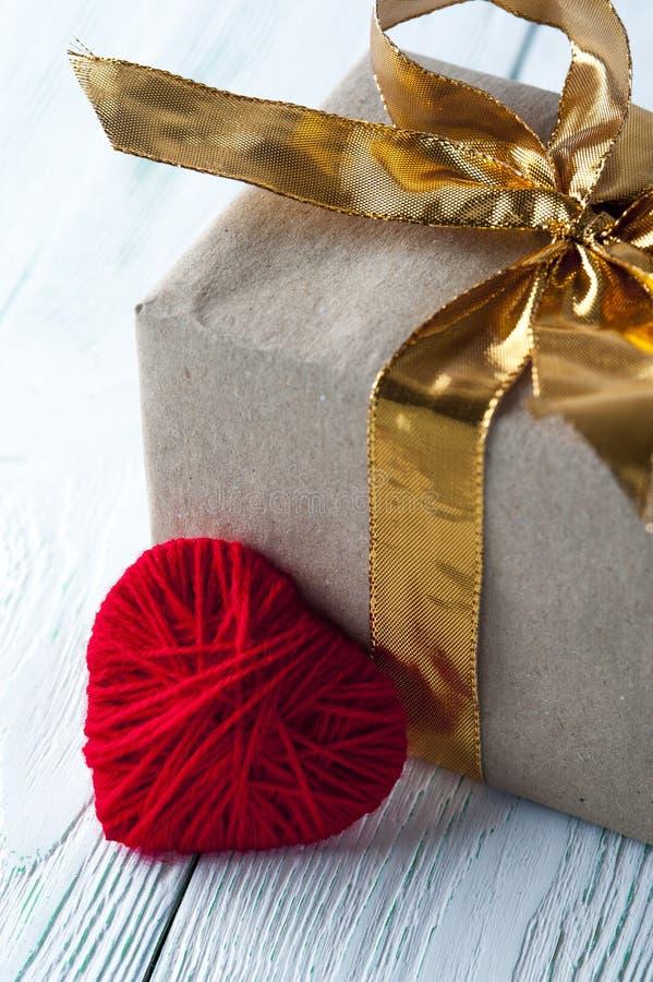 El rojo hizo punto el corazón, caja de regalo en fondo rústico foto de archivo libre de regalías