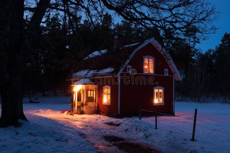 El rojo pintó la casa de madera en Suecia en la noche imagenes de archivo