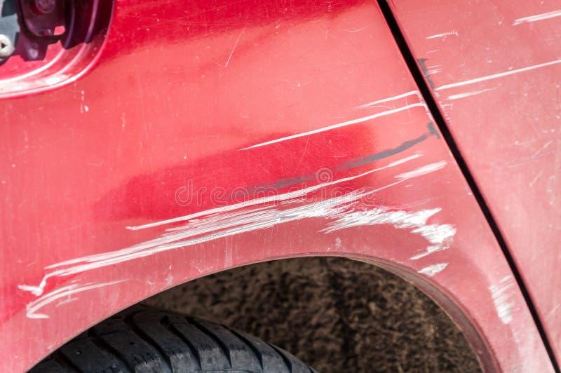 El rojo rasguñó el coche con la pintura dañada en accidente del desplome en la calle o el estacionamiento en la ciudad fotos de archivo