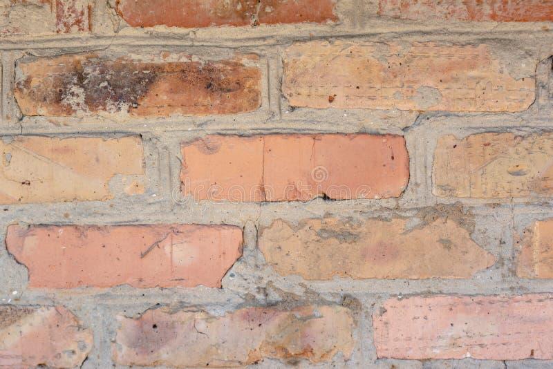 El rojo se descoloró viejo fondo de los ladrillos con los defectos y las fracturas imagenes de archivo