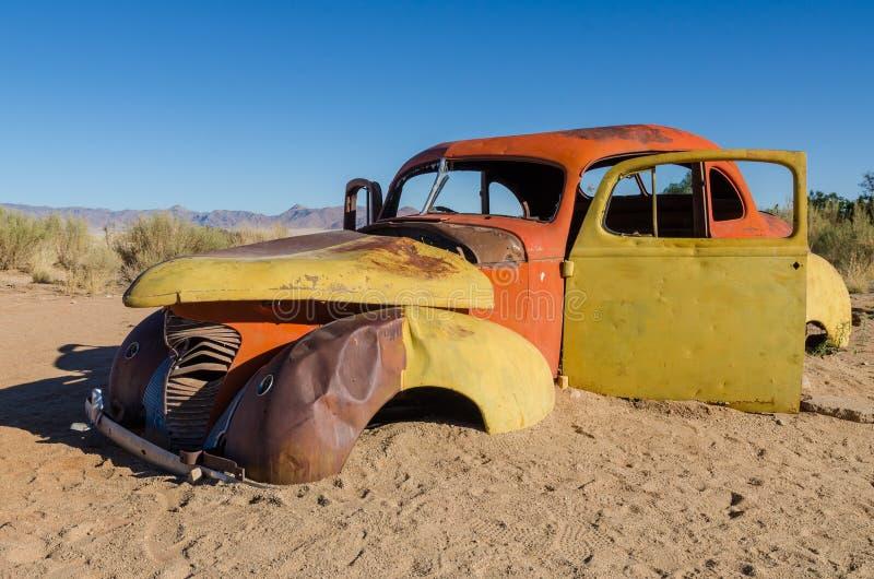 El rojo y el amarillo abandonaron el coche clásico en el desierto de Namib cerca del solitario, Namibia imágenes de archivo libres de regalías