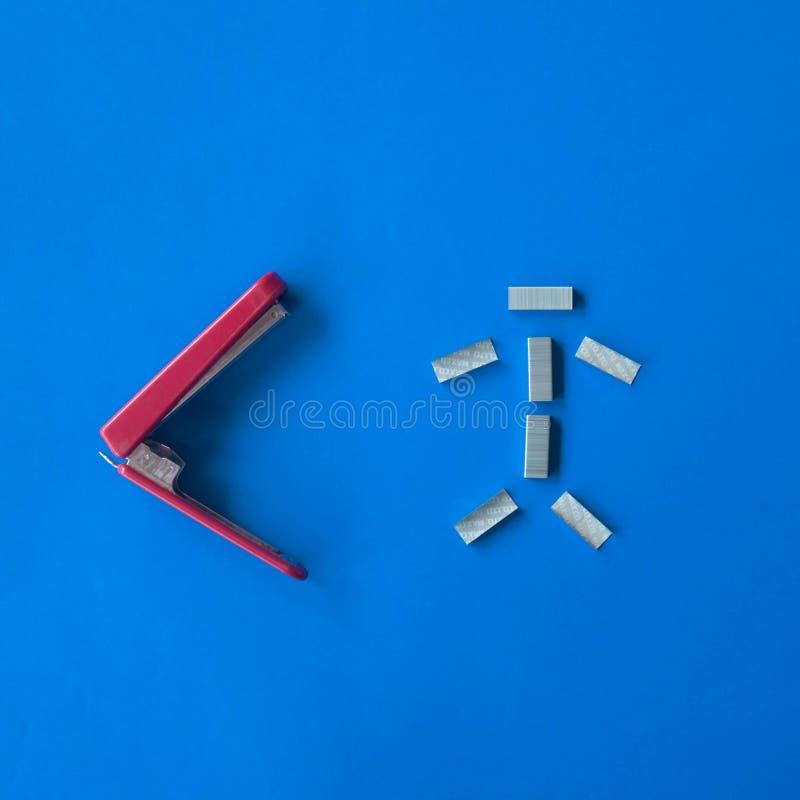 El rojo y el blanco aislaron la herramienta de la grapadora del metal en fondo azul imagen de archivo