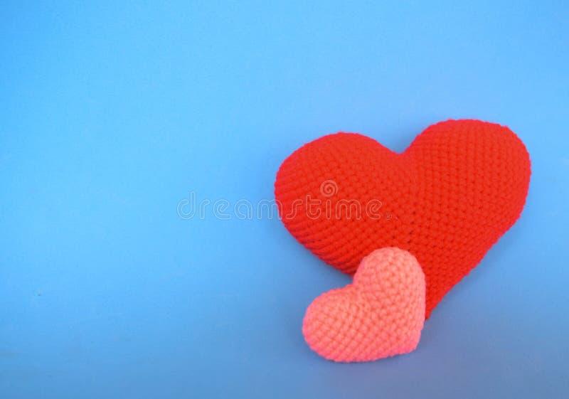 El rojo y el rosa hacen a ganchillo forma del corazón en fondo azul Símbolo del concepto del día del ` s de la tarjeta del día de foto de archivo