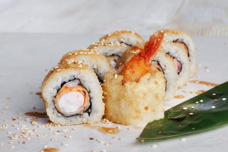 El rollo con tempura del camarón en las hojas tropicales de la tabla del verde de la hoja del unagi de la salsa de una rebanada d fotos de archivo libres de regalías