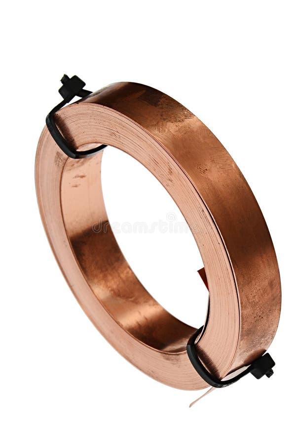 El rollo de la tira de cobre eléctrica fina limitó con el ajuste de las correas plásticas negras, fondo blanco fotografía de archivo libre de regalías
