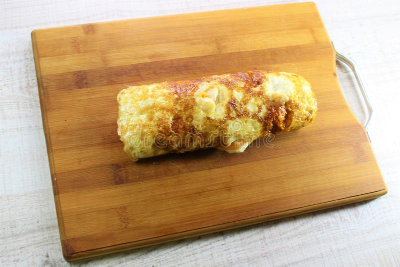 El rollo de la tortilla de los huevos fritos llenó de queso y del calabacín con el fondo de madera blanco fotografía de archivo