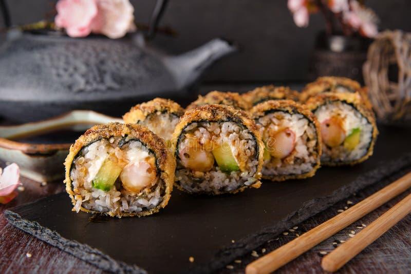 El rollo de sushi frito caliente con el camarón, el pepino y el unagi sauce foto de archivo
