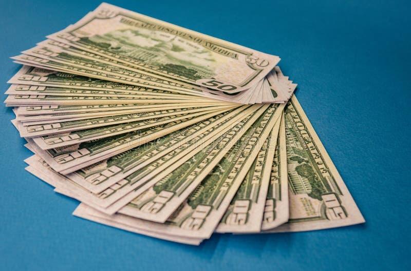 El rollo gordo grande del dinero aisl? en un fondo azul foto de archivo