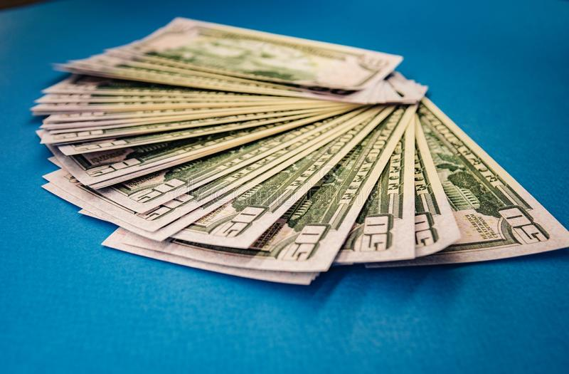 El rollo gordo grande del dinero aisl? en un fondo azul imágenes de archivo libres de regalías