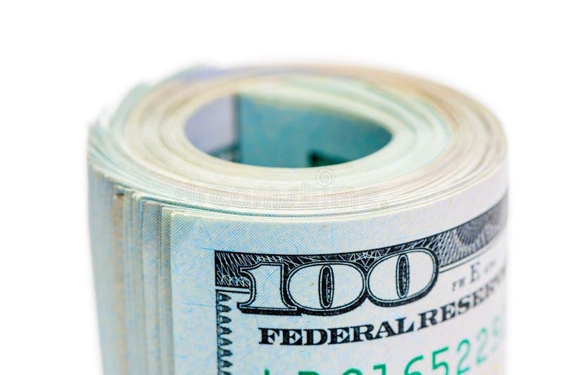 El rollo macro de rodó para arriba 100 billetes de dólar y apretado por la goma en el fondo blanco imágenes de archivo libres de regalías