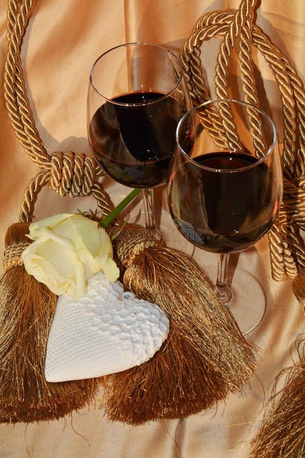 El romance, subió, el corazón, vidrios de vino rojo foto de archivo