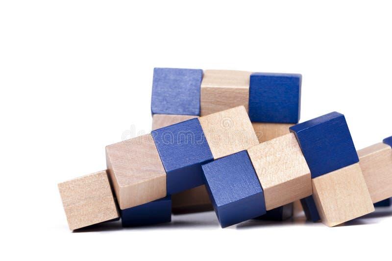 El rompecabezas desafiador de la mente compleja, los cubos de madera azules juega aislado en el fondo blanco imagenes de archivo