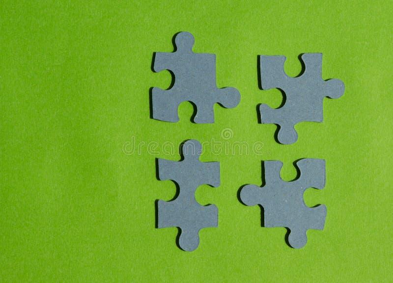 El rompecabezas junta las piezas en el fondo verde claro, visión horizontal fotografía de archivo