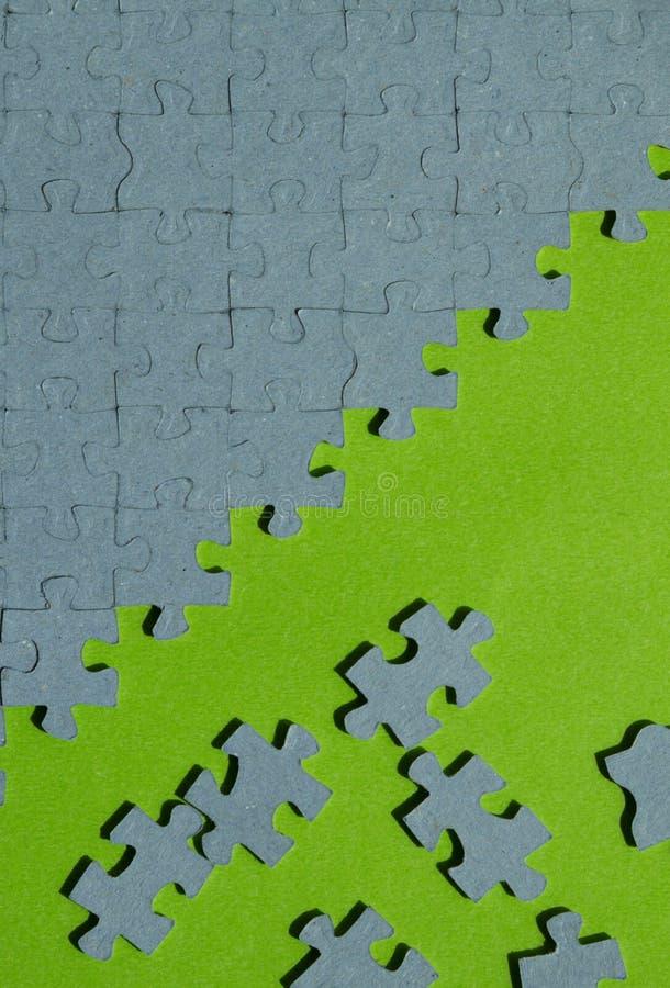 El rompecabezas junta las piezas en fondo verde con el espacio de la copia fotos de archivo