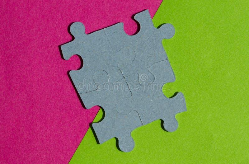 El rompecabezas junta las piezas en la frontera entre el fondo rosado y verde fotografía de archivo libre de regalías