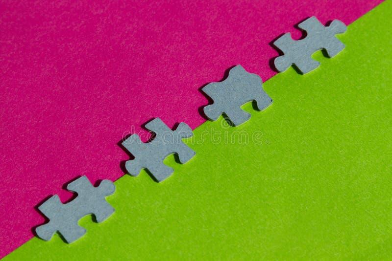 El rompecabezas junta las piezas en la frontera entre el fondo rosado y verde imágenes de archivo libres de regalías