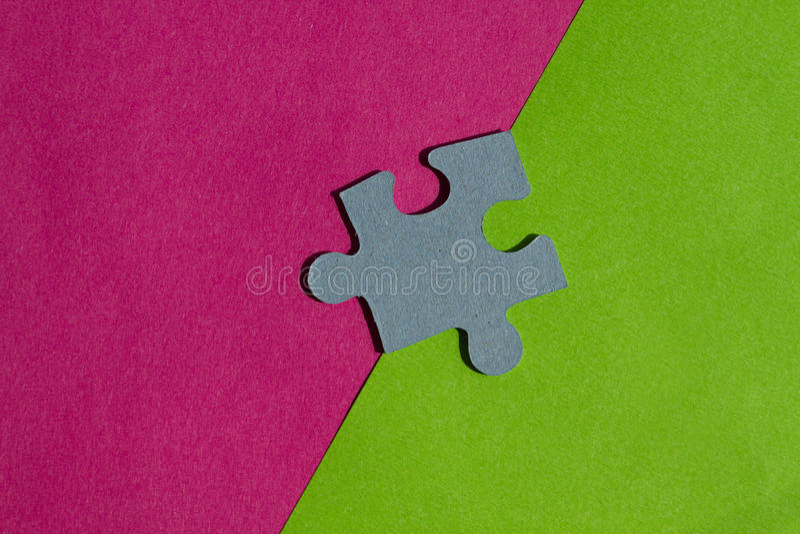 El rompecabezas junta las piezas en la frontera entre el fondo rosado y verde fotos de archivo