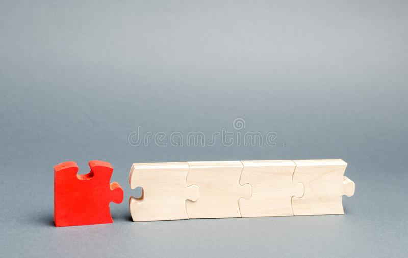 El rompecabezas rojo se desconecta del resto el concepto de individualidad y de unicidad opini?n individual Traici?n en foto de archivo libre de regalías