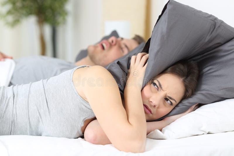 El roncar del hombre y sus oídos de la cubierta de la esposa imagen de archivo