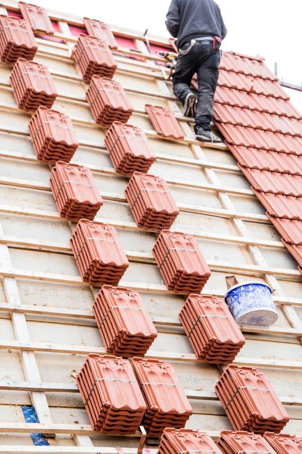 El Roofer que trabaja en la estructura de tejado del edificio en la construcción se sienta imagen de archivo