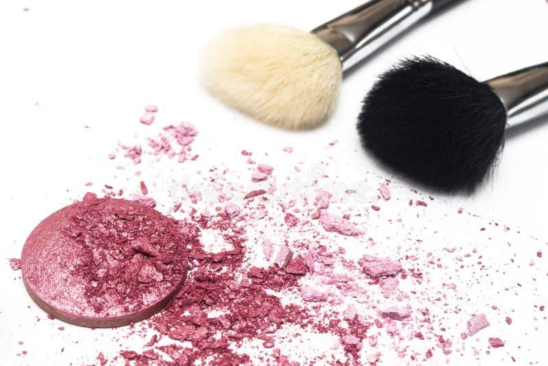 El rosa de color salmón machacado se ruborizan y los cepillos del cosmético en el fondo blanco fotos de archivo