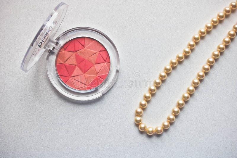 El rosa de la paleta se ruboriza Make up se ruboriza mosaico con el collar de la perla en el fondo blanco fotos de archivo