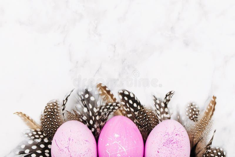 El rosa pintado de Pascua eggs con las plumas elegantes en un fondo de mármol Fondo del día de fiesta foto de archivo