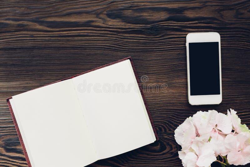 El rosa plano de la endecha florece, teléfono móvil y diario en el fondo de madera, visión superior Mofa para arriba imagen de archivo libre de regalías