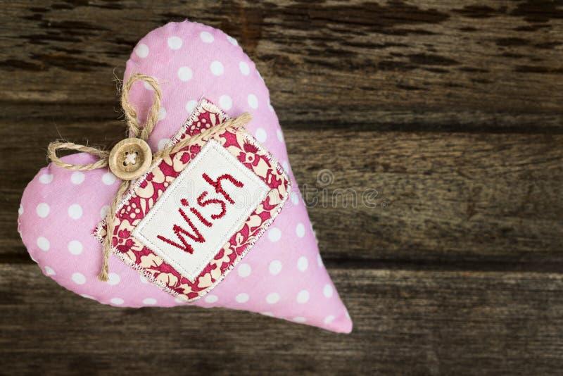 El rosa punteó el corazón hecho a mano de la tela con la palabra DESEO en backg de madera imagenes de archivo