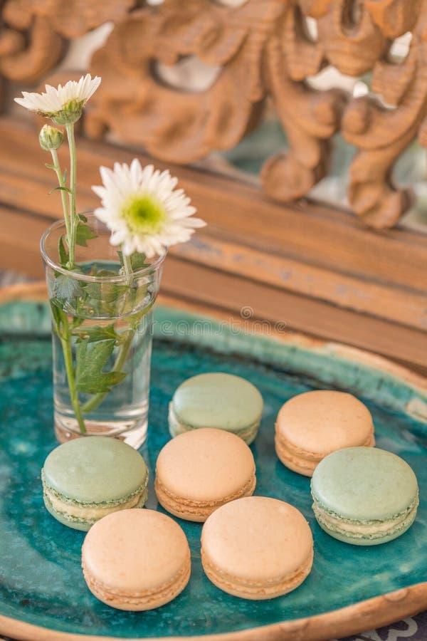 El rosa y palidece - los macarrones verdes en una placa de cerámica verde fotografía de archivo libre de regalías