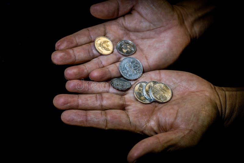 El rupia de Indonesia acuña en la mano de una persona asiática aislada imagenes de archivo