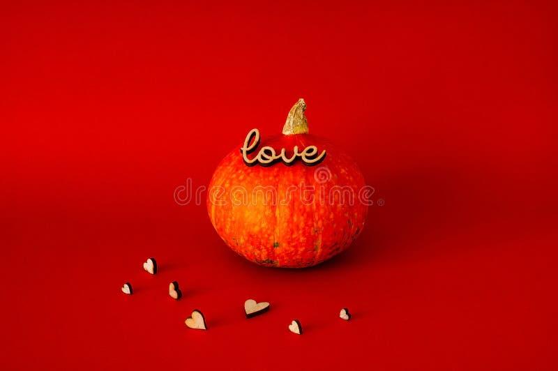 El símbolo de HALLOWEEN es calabaza anaranjada usando el ` del amor del ` del sello, en fondo rojo, espacio de la copia fotos de archivo