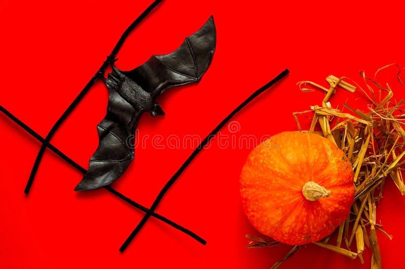 El símbolo de HALLOWEEN es calabaza y palo anaranjados en fondo rojo fotografía de archivo libre de regalías