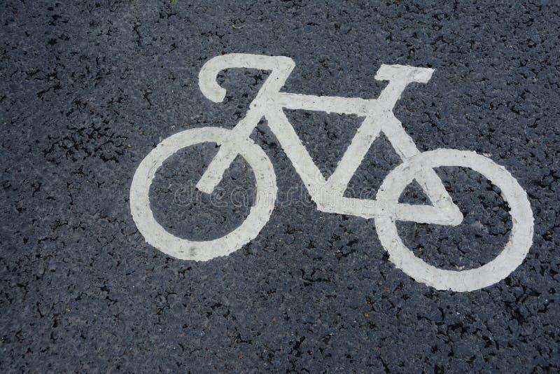 El símbolo de la bicicleta dibujado en el asfalto de una marca de la pista de la bicicleta fotografía de archivo