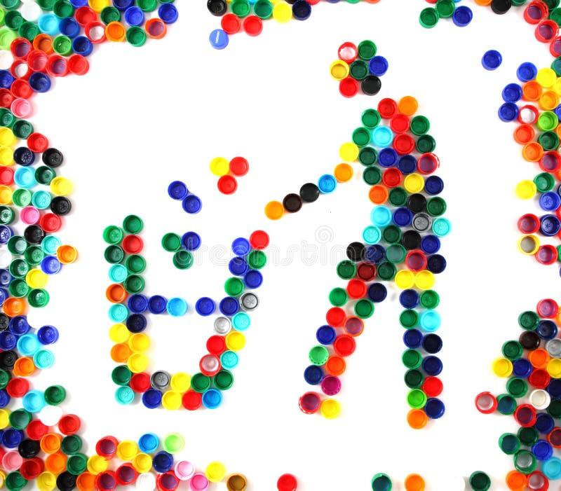 El símbolo recicla de los casquillos del plástico del color foto de archivo libre de regalías