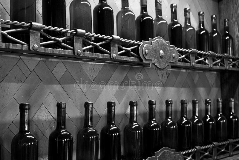 El sótano deja de lado con las botellas de vino tapadas con corcho oscuras contra monocromo blanco y negro de la pared de madera imagen de archivo