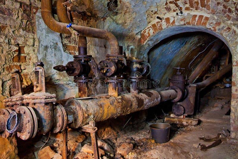 El sótano subterráneo saltado del ladrillo rojo con la calefacción por agua oxidada instala tubos imágenes de archivo libres de regalías