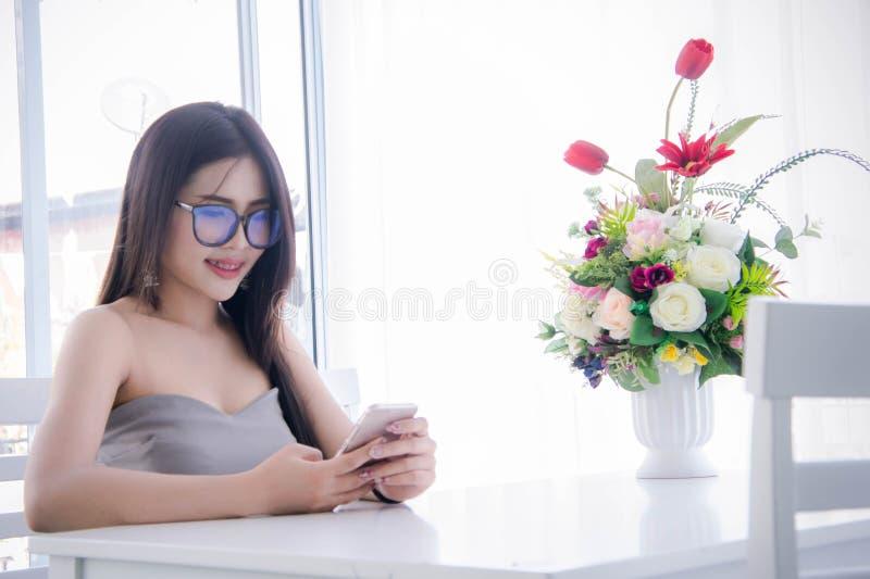 El ` s de la muchacha que mira y goza de smartphone en su sittin de la mano y de la risa imagen de archivo libre de regalías