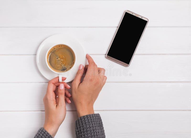 El ` s de la mujer da sostener la taza de café y de smartphone que mienten cerca foto de archivo libre de regalías