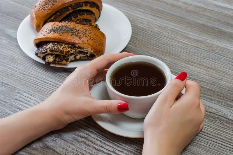 El ` s de la mujer da la taza conmovedora del té, bollos con las semillas de amapola en fotos de archivo libres de regalías
