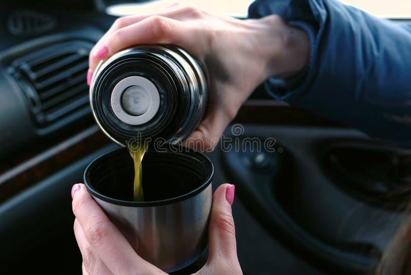 El ` s de la mujer del primer da la colada de un té caliente en una taza del termo en el coche en invierno fotografía de archivo libre de regalías