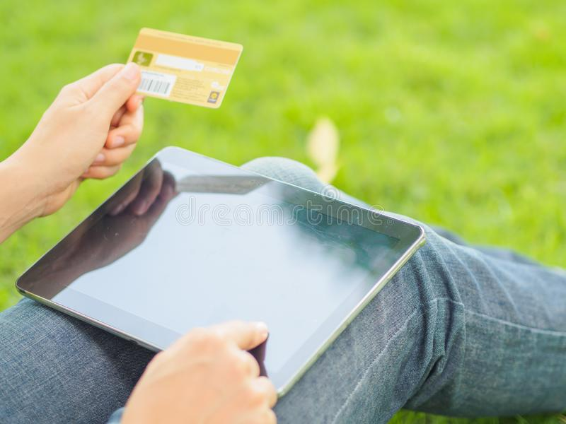 El ` s de la mujer del primer da sostener una tarjeta de crédito y usar la PC de la tableta para las compras en línea fotografía de archivo