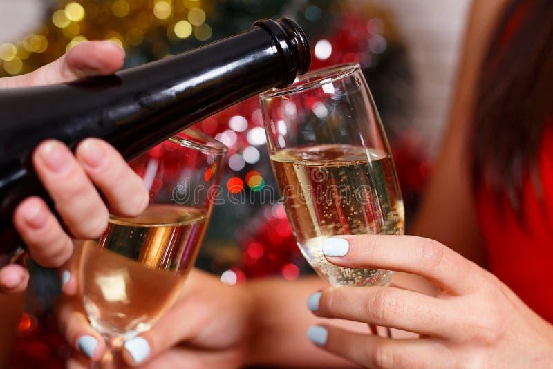 El ` s de las mujeres da el champán de colada en los vidrios, cierre para arriba Celebrat foto de archivo libre de regalías