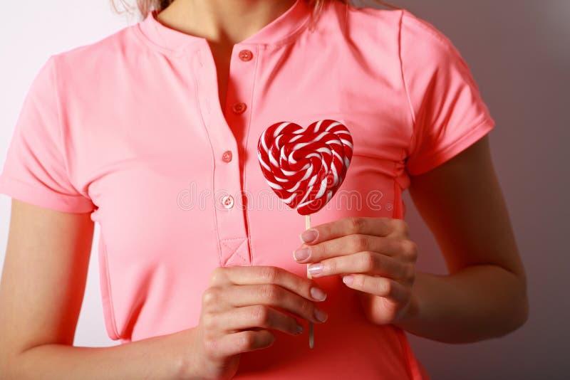 El ` s de las mujeres da sostener una piruleta en la forma de corazón Regalo para fotografía de archivo