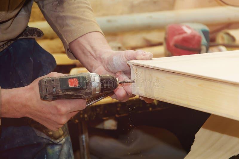 El ` s del carpintero da la madera de la perforación del trabajador del hombre en el emplazamiento de la obra imagen de archivo