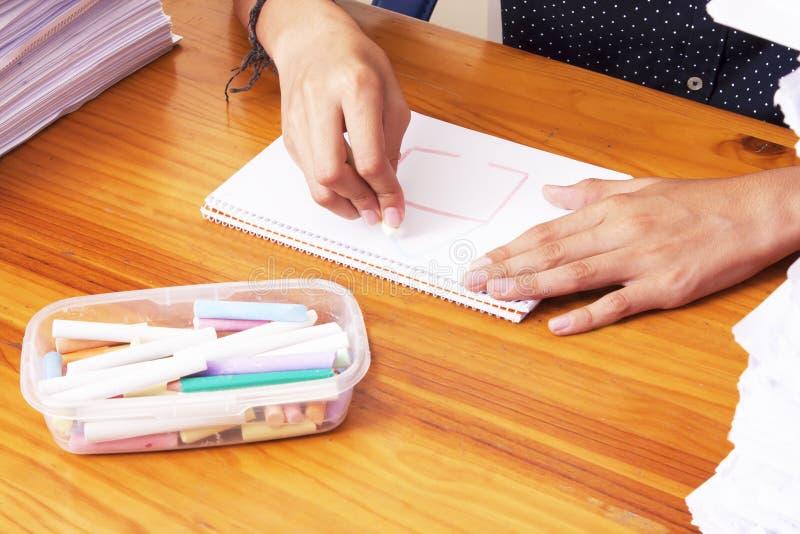El ` s del estudiante da el dibujo o la escritura en la escuela imagen de archivo