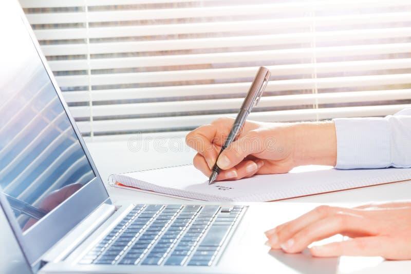 El ` s del estudiante da la fabricación de notas al lado del ordenador portátil fotografía de archivo libre de regalías