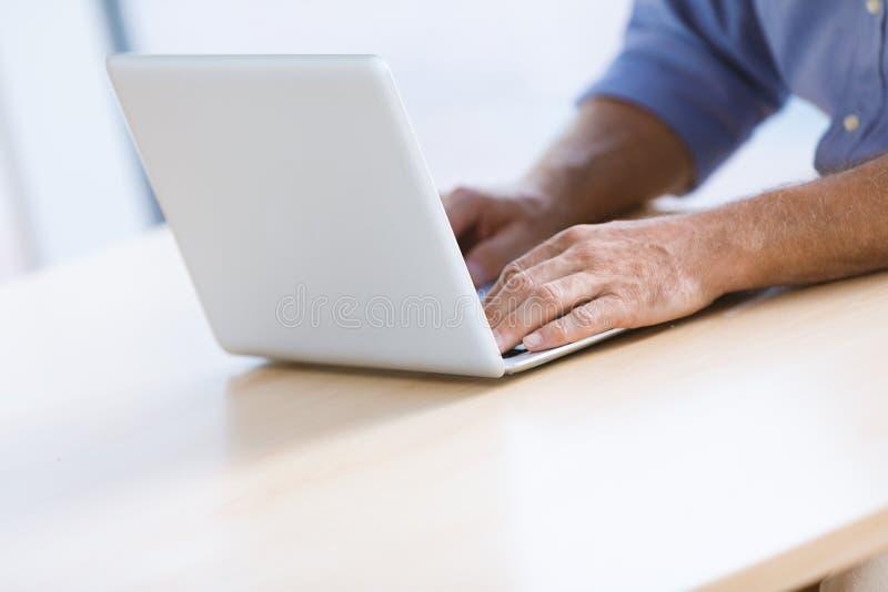El ` s del hombre de negocios da mecanografiar lejos en el teclado de ordenador portátil foto de archivo