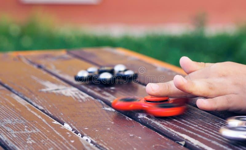 El ` s del niño pequeño da jugar con un primer del hilandero de la persona agitada Juguete popular y de moda para los niños y el  fotos de archivo libres de regalías