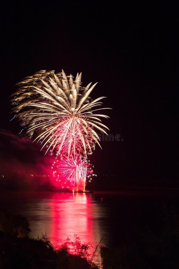 El ` s Eve Fireworks del Año Nuevo lanzó del agua con reflexiones imagen de archivo